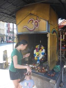 If your gods don't produce the goods, pray to someone else's. Chinese woman prays to Ganesh.