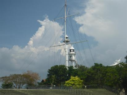 Flag mast and lighthouse next to Fort Cornwallis.